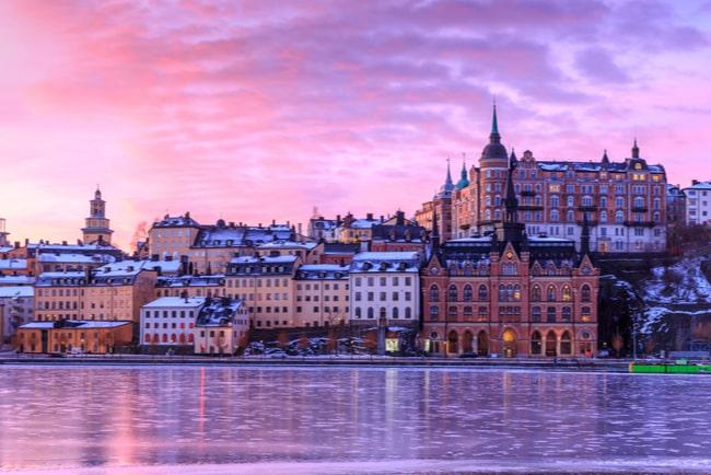 vy över södermalm i stockholm med rosa himmel som reflekteras i vattnet