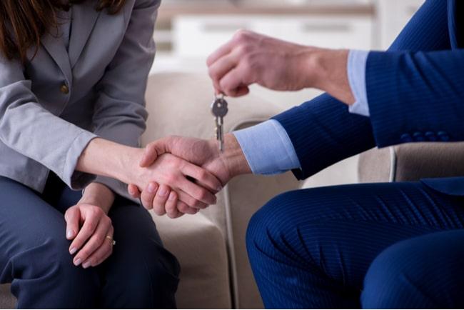 Kvinna skakar hand med en man som räcker över en nyckel.