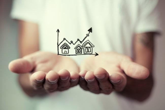 Närbild på en persons händer som håller upp svävande teckning på hus och stigande graf.