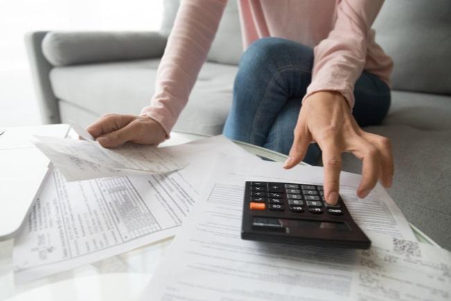 kvinna sitter med papper och miniräknare i soffan