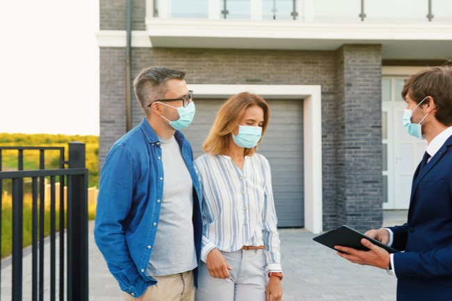 Två bostadsköpare och en mäklare i munskydd framför ett hus.