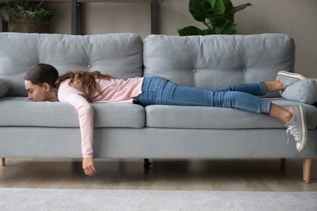 Ung tjej i blå jeans och rosa tröja ligger på en grå soffa.