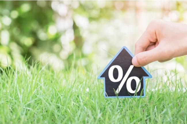 Hand sätter ner hussymbol med procenttecken i gräset.